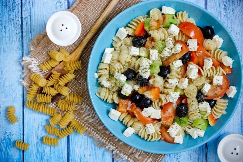 Griekse salade met verse groenten, feta-kaas, deegwaren en zwarte olijven stock foto's
