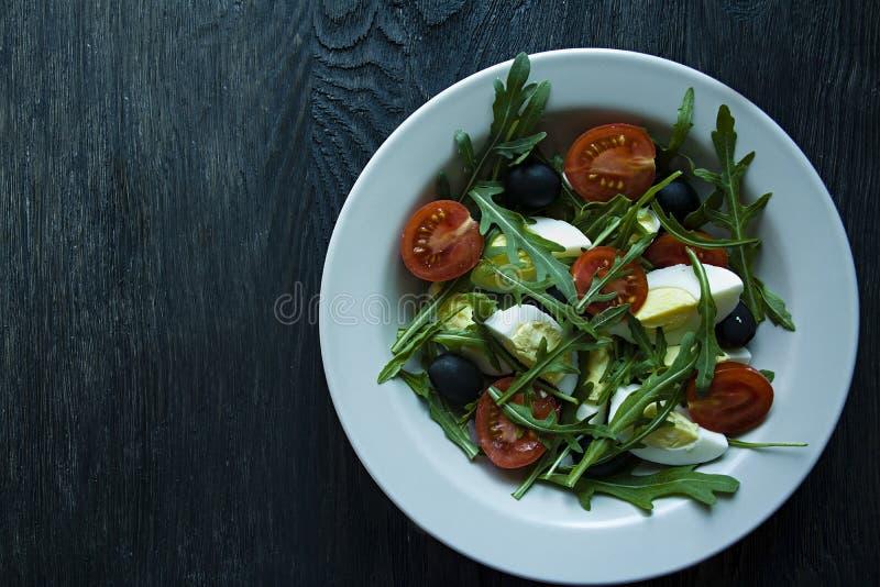 Griekse salade met verse tomaten, arugula, eieren, olijven met olijfolie op een donkere houten achtergrond Gezond voedsel Veggie  stock afbeelding