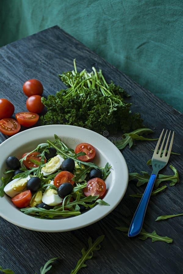 Griekse salade met verse tomaten, arugula, eieren, olijven met olijfolie op een donkere houten achtergrond Gezond voedsel Veggie  stock foto