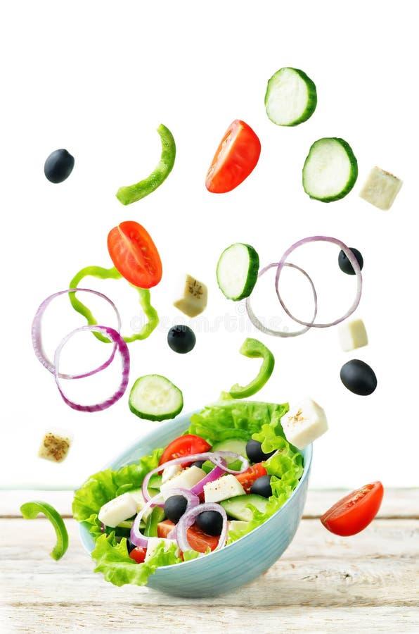 Griekse Salade met vliegende ingrediënten om het voor te bereiden royalty-vrije stock foto