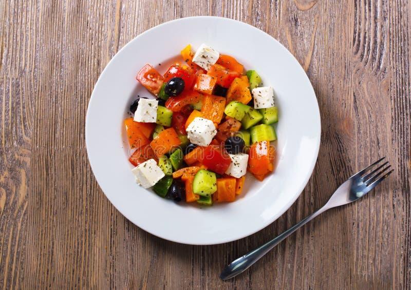 Griekse salade van verse komkommer, tomaat, paprika, feta-kaas en olijven met olijfolie en kruiden Gezond voedsel, hoogste mening royalty-vrije stock fotografie