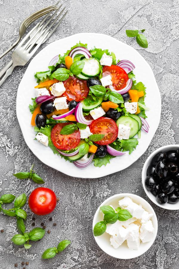 Griekse Salade Verse groentesalade met tomaat, ui, komkommers, basilicum, peper, olijven, sla en feta-kaas Griekse salade op p stock fotografie