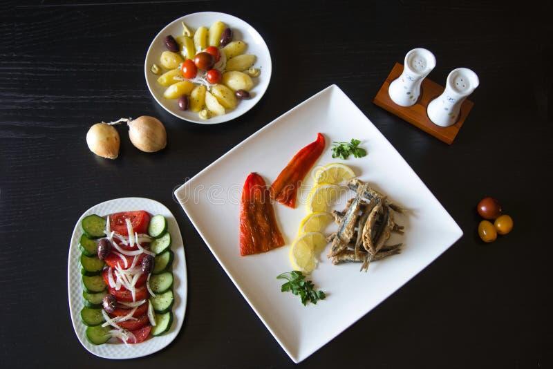 Griekse traditionele gebraden ansjovissengavros met een gesneden citroen op een plaat, een Griekse salade en gekookte aardappels  royalty-vrije stock afbeelding