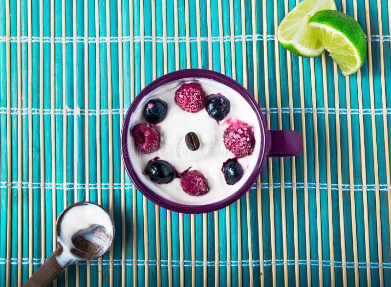 Griekse yoghurt met bosbessen en frambozen met citroen of citrusvrucht op een rustieke zachte blauwe achtergrond de zomeruitgave royalty-vrije stock afbeeldingen