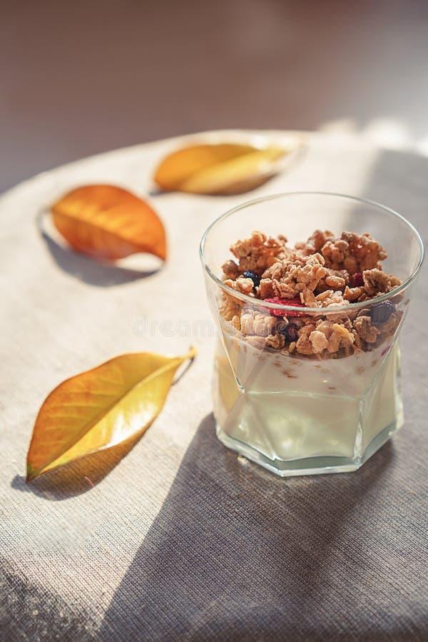 Griekse yoghurt met granola, droge bessen in glas en gele bladeren Grijze achtergrond met rustieke stijldoek De hoogste ruimte va royalty-vrije stock afbeeldingen