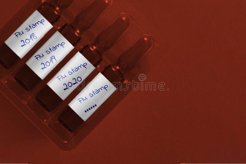 Griep epidemisch concept Vier ampules met bekleding overhandigen geschreven inschrijving van nieuwe Griepzegel en jaren Pharmabio stock afbeeldingen
