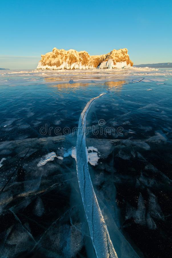 Grieta grande en el hielo liso que va a la isla Lago Baikal del invierno imagenes de archivo