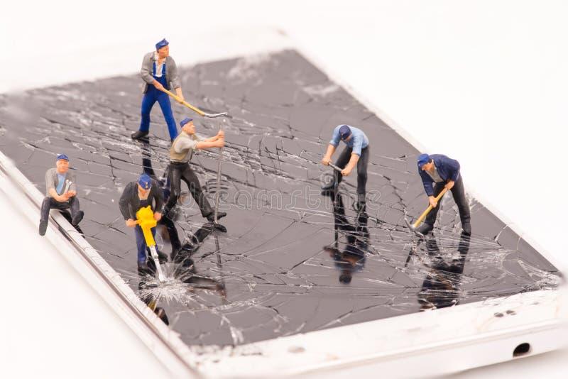 Grieta miniatura del smartphone de la reparación de la gente foto de archivo