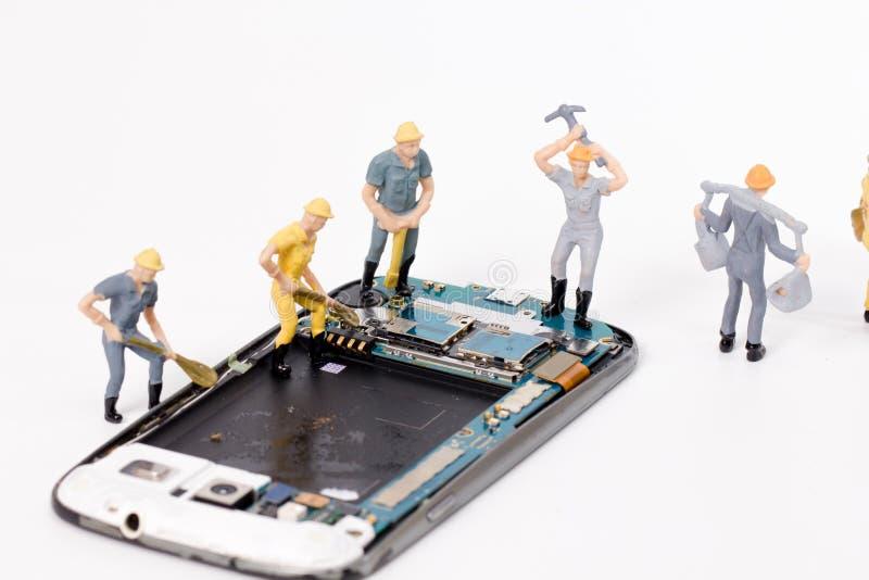 Grieta miniatura del smartphone de la reparación de la gente imágenes de archivo libres de regalías