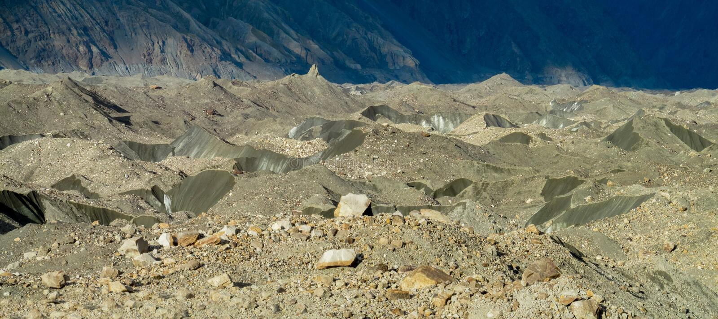 Grietas e hielo del glaciar cubiertos con las piedras grises del morena imágenes de archivo libres de regalías