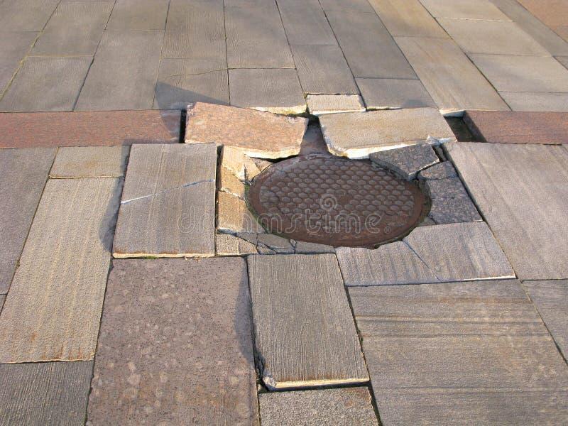 Grietas en tejas de la calle imagen de archivo