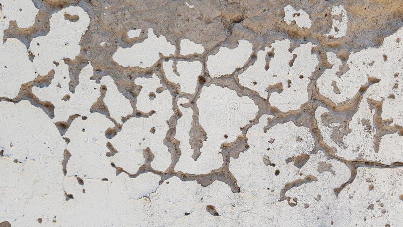 Grietas grises y pequeños agujeros en la superficie rasguñada blanca imagenes de archivo