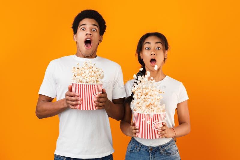 Griezelfilm Bang gemaakt paar die popcorn over achtergrond werpen royalty-vrije stock foto