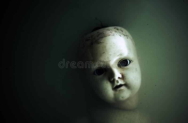 Griezelig poppengezicht in donker water stock fotografie