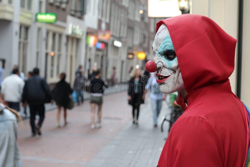 Griezelige clown die zijn slachtoffer in overvolle plaats zoeken royalty-vrije stock fotografie
