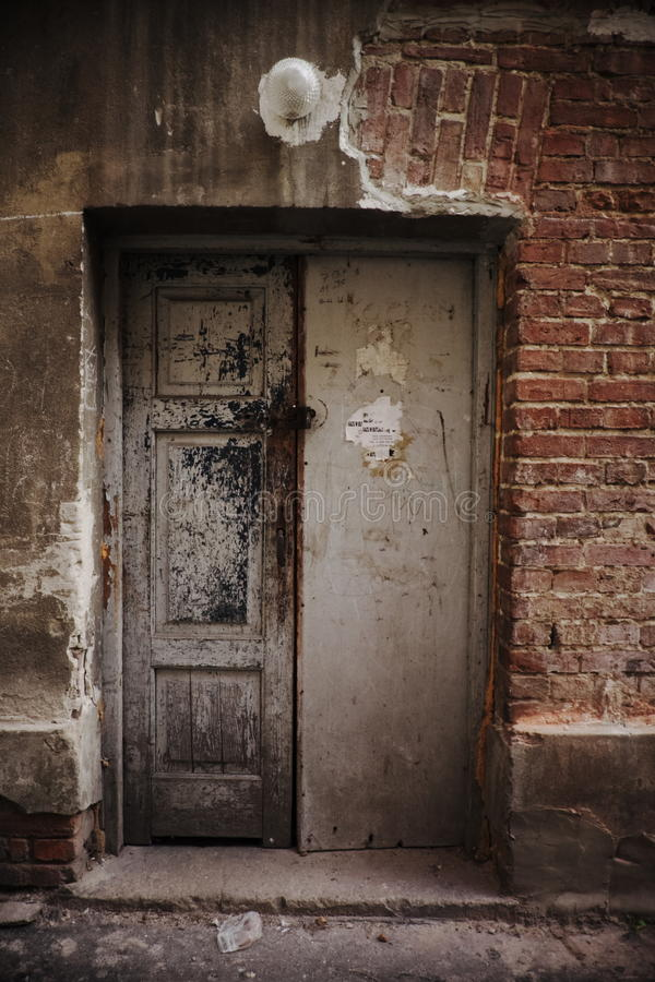 Griezelige deur in de beschadigde bouw in krottenwijkdistrict stock afbeelding