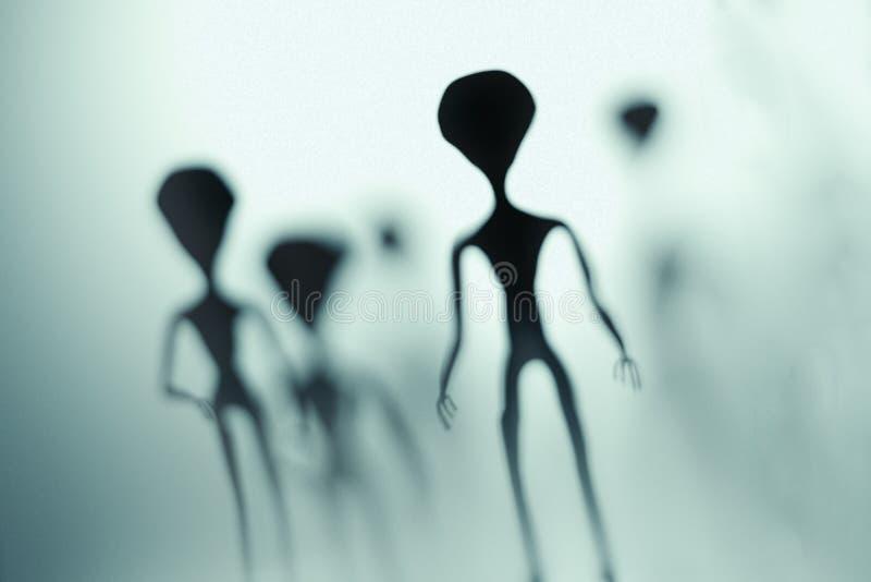 Griezelige silhouetten van vreemdelingen en helder licht op achtergrond 3D teruggegeven illustratie stock illustratie