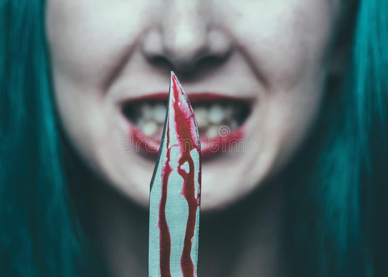 Griezelige vrouw met mes in bloed stock afbeelding