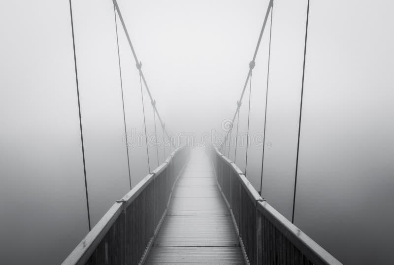 Griezelige Zware Mist op Hangbrug die in Griezelige Onbekend verdwijnen royalty-vrije stock afbeelding
