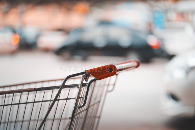 Griff des Einkaufswagens und des unscharfen Autos am Parkplatz stockbild