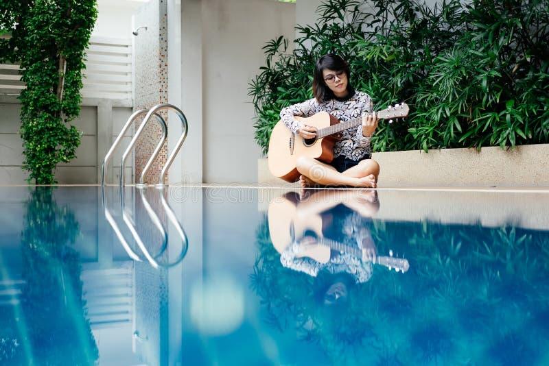 Griffgitarrenklassiker der jungen Frau in ihrer Hand und Sitzen neben p stockbilder