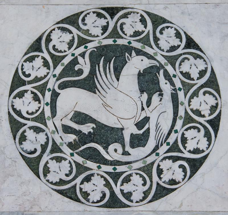 Griffin mythical animal in a decorative circle on the Chiesa dei Santi Giovanni e Reparata. Griffin mythical animal in a decorative circle. nThis is a decorative royalty free stock photos