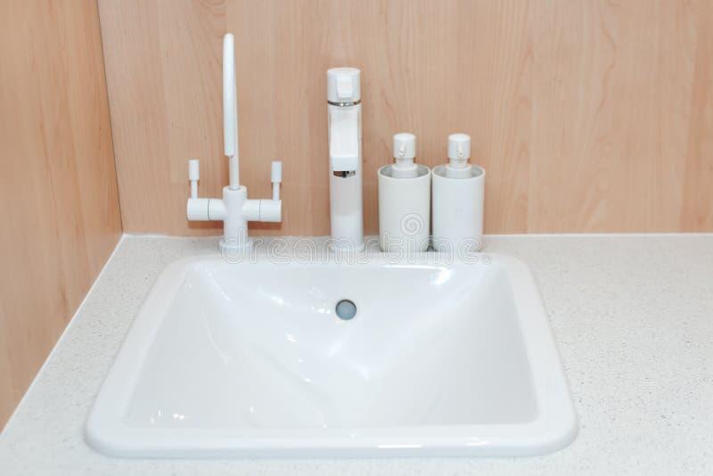 Grifo blanco de la cocina moderna y fregadero de cocina de cerámica Detalles interiores del cuarto de baño minimalista foto de archivo libre de regalías