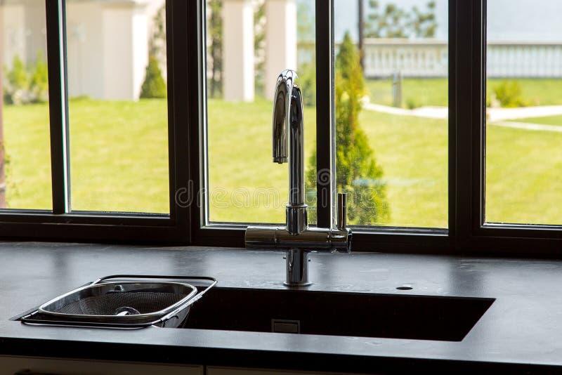 Grifo cromado en el fregadero de cocina con un tablero de la mesa de piedra negro foto de archivo