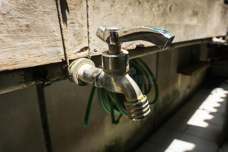 Grifo del acero inoxidable con la línea del tubo de agua en una pared de ladrillo Duri admitido foto Tangerang Indonesia imagen de archivo libre de regalías