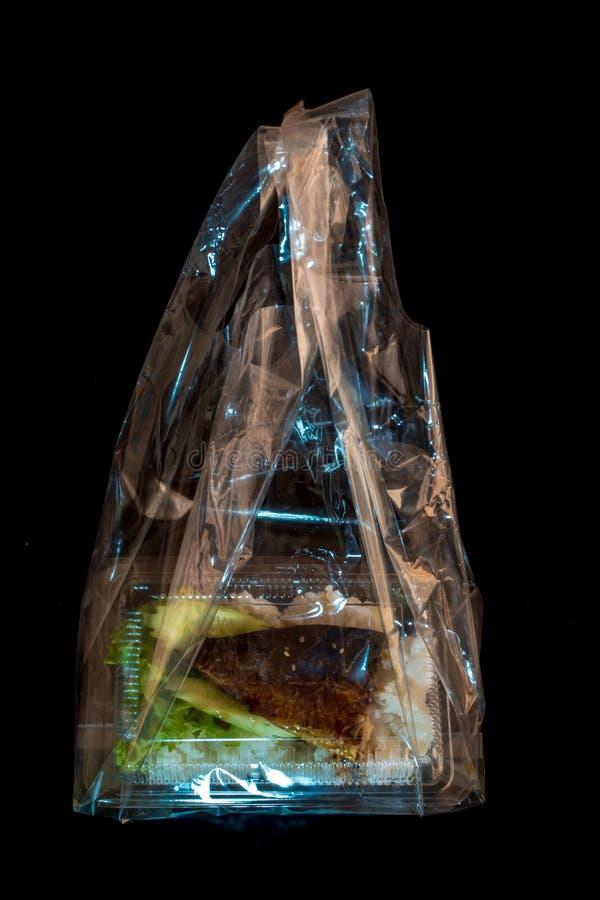 Grigli il pesce su riso in scatola di plastica, alimento netto immagine stock