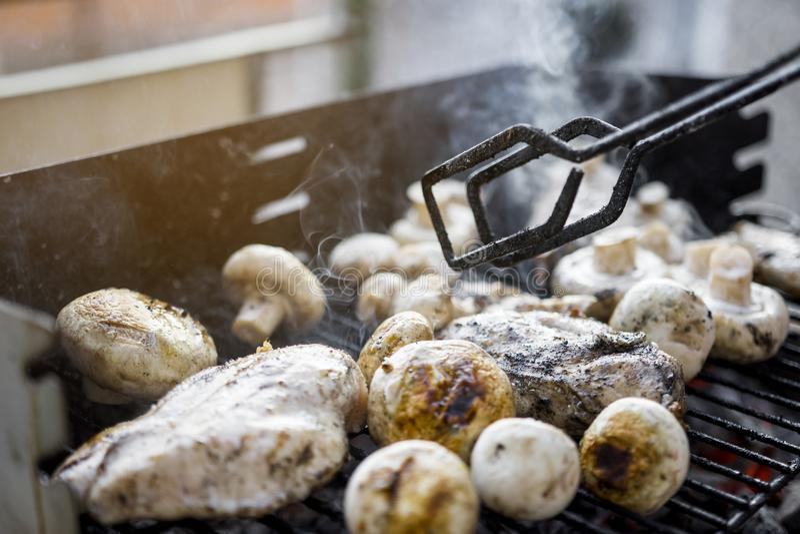 Griglia del BBQ con molti funghi e petto di pollo saporito fotografie stock