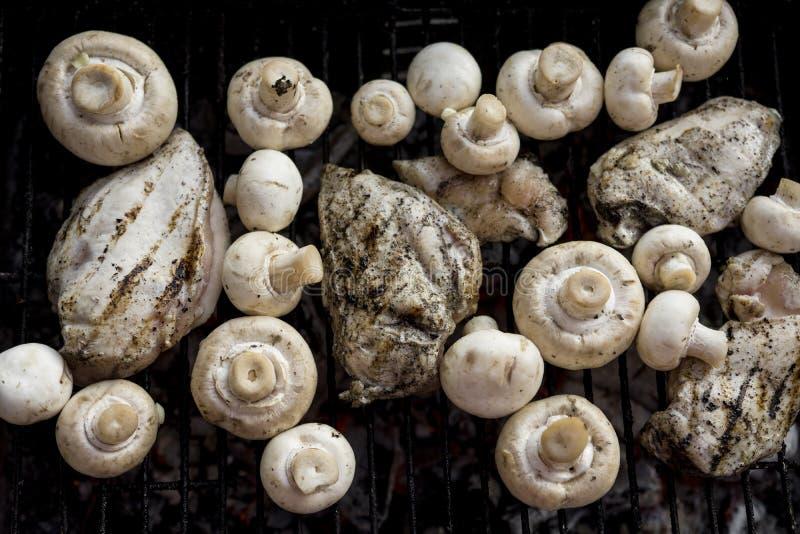 Griglia del BBQ con molti funghi e petto di pollo saporito immagini stock libere da diritti
