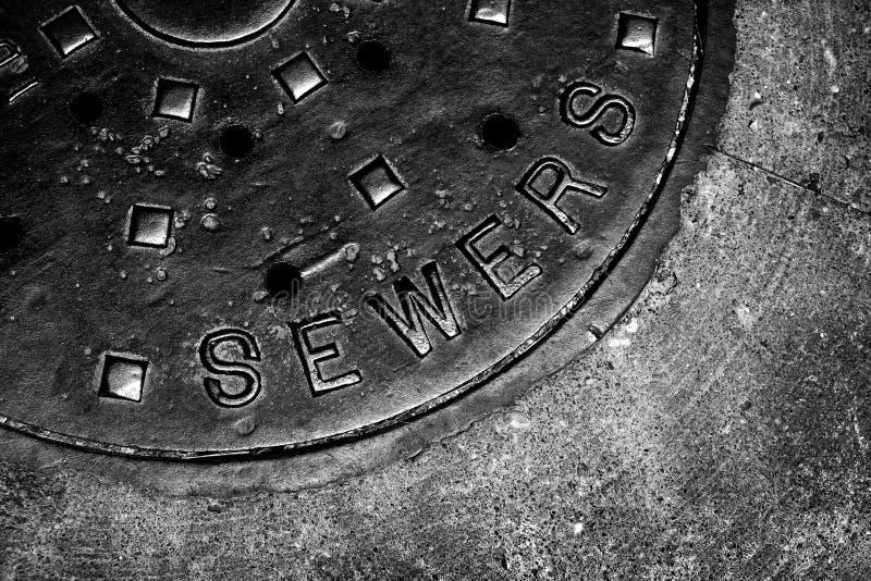 Griglia del ferro del foro dell'uomo della copertura della fogna sulla via in città immagini stock libere da diritti