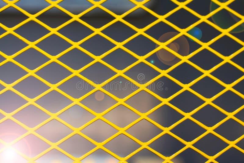 Griglia del metallo giallo sui precedenti scuri, tonificati con luce solare immagini stock libere da diritti