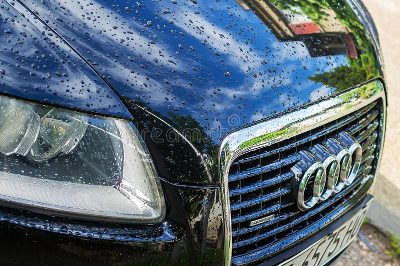 Griglia dell'automobile di Audi con il logo ed il cofano anteriore del cromo con le gocce di pioggia e riflessione del cielo e de fotografie stock libere da diritti