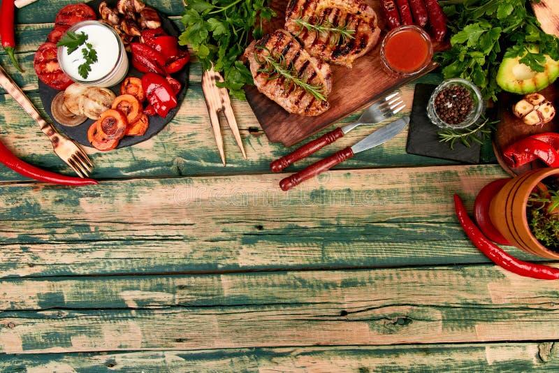 Griglia della carne di maiale della bistecca sul tagliere di legno con varie verdure arrostite immagine stock