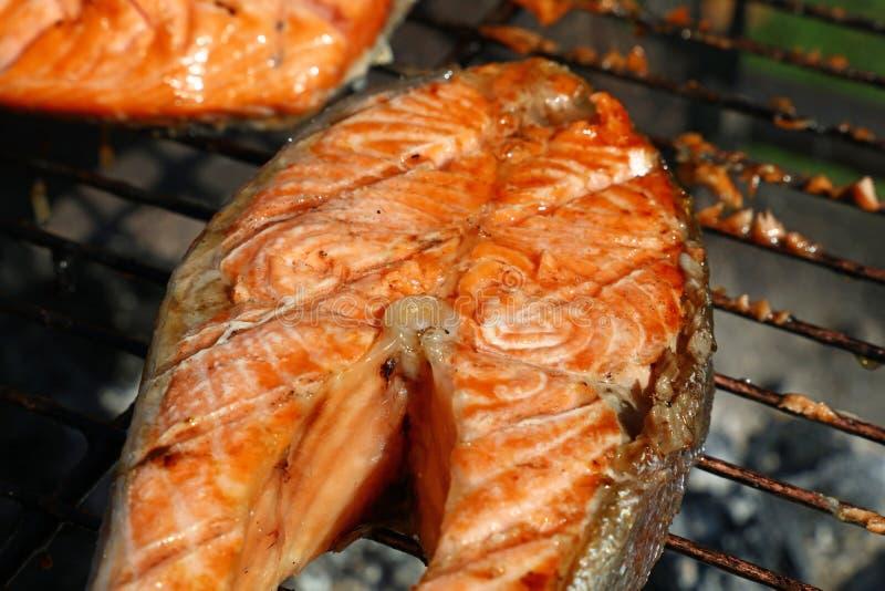 Griglia di color salmone del barbecue del trancio di pesce che cucina vicino su immagini stock