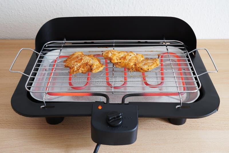 Griglia elettrica della tavola con il pollo arrostito fotografia stock libera da diritti