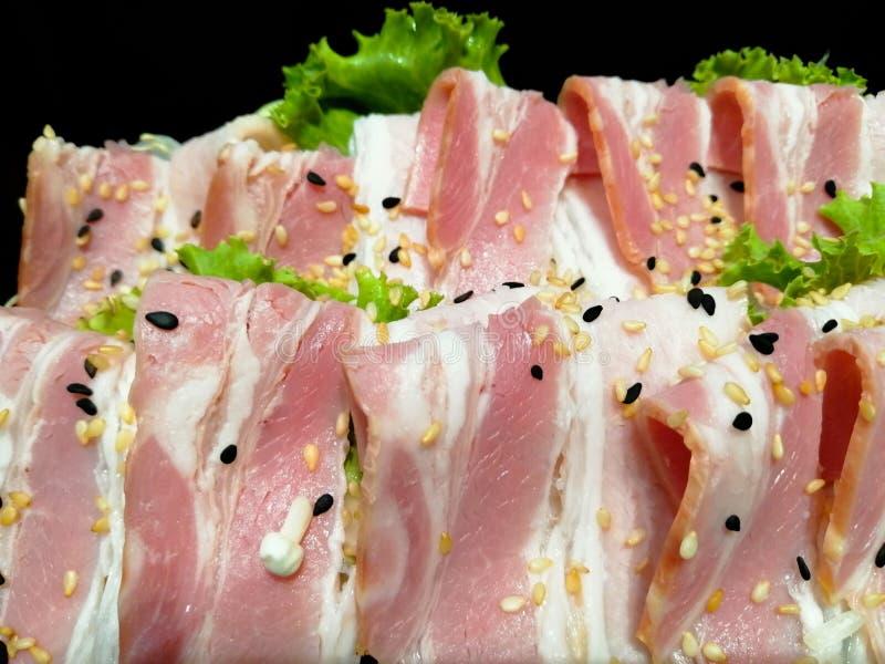 Grigliare e barbecue - lo scorrevole la pancia di carne di maiale nelle strisce sottili, ha messo su un piattino nero con, decora fotografia stock