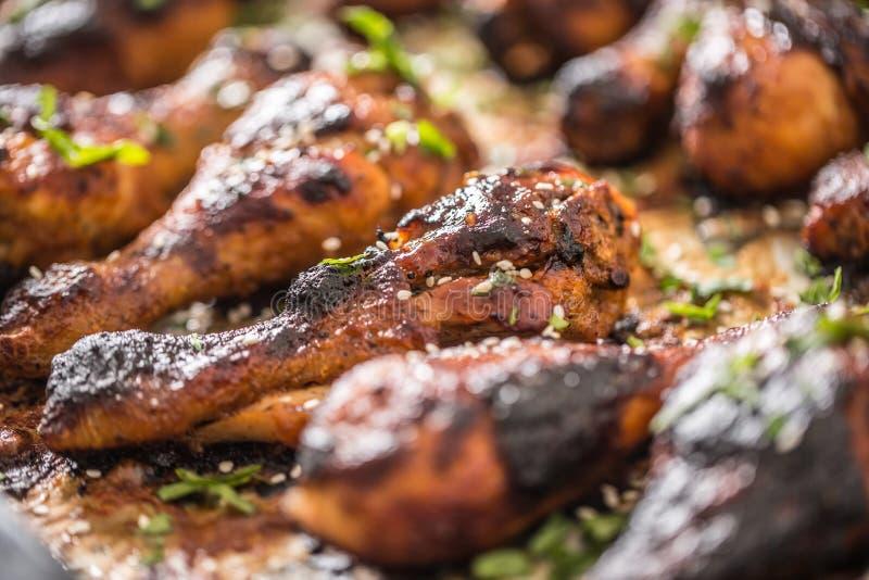 Grigliato hicken il BBQ delle gambe con le erbe ed il sesamo delle spezie su carta al forno Pasto arrostito del pollame nel piatt immagine stock libera da diritti