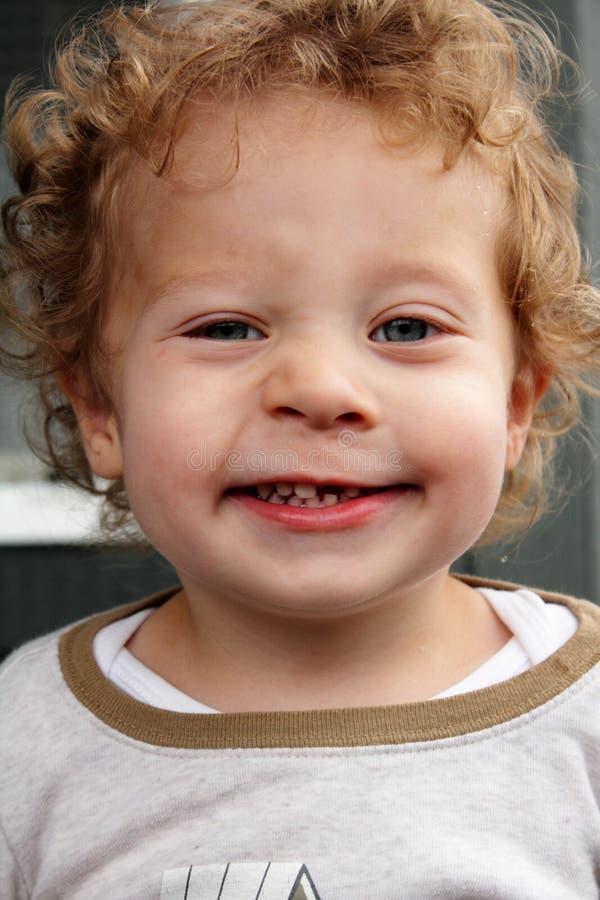 Grijnzende 2 jaar oude blonde jongen die een tand mist stock afbeeldingen