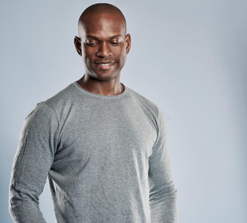 Grijnzende Afrikaanse mens in grijs overhemd met exemplaarruimte stock foto
