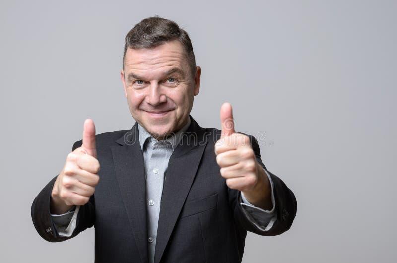 Grijnzende mens in kostuumjasje met twee omhoog duimen stock fotografie
