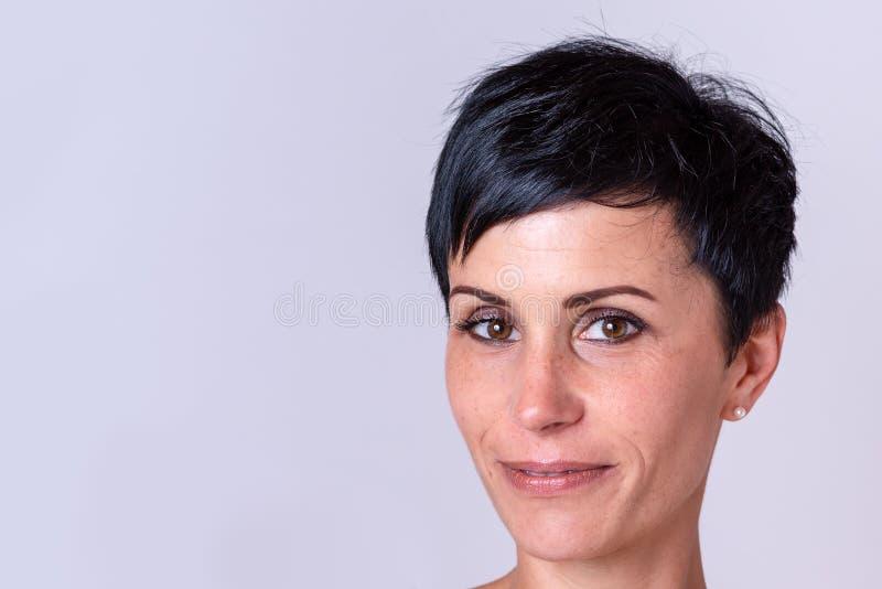 Grijnzende volwassen vrouw over neutrale achtergrond stock fotografie