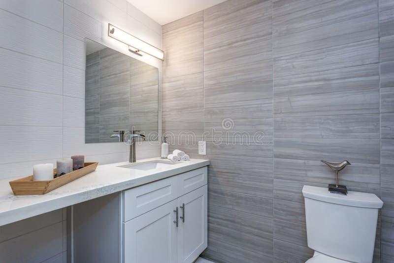 Grijs binnenland van een nieuwe badkamers in flatgebouw stock afbeeldingen