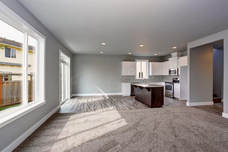 Grijs die huisbinnenland van keukenruimte aan de woonkamer wordt verbonden stock afbeelding