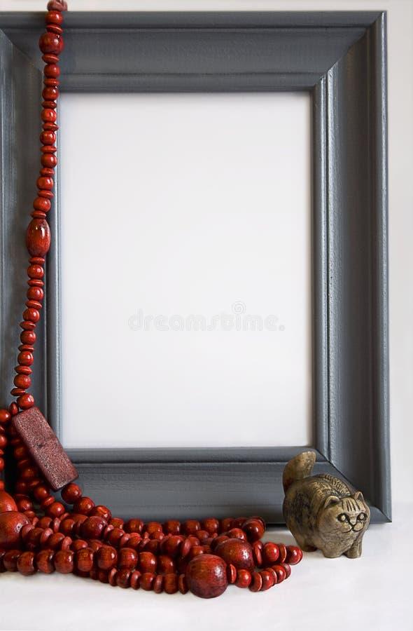 Grijs frame met rode parels en steen met de hand gemaakte kat stock foto's