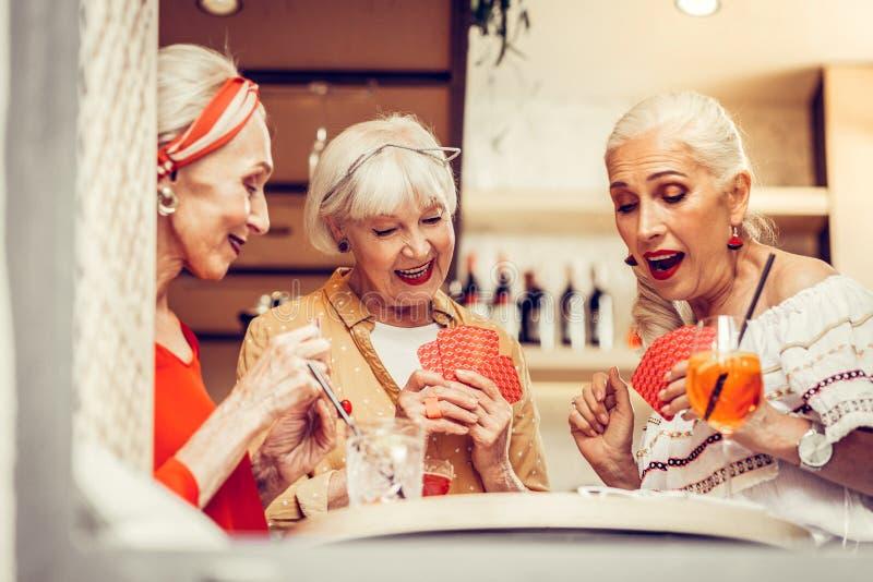 Grijs-gehuurde modieuze uitrustingen dragen en actief dames die samen spelen stock afbeeldingen