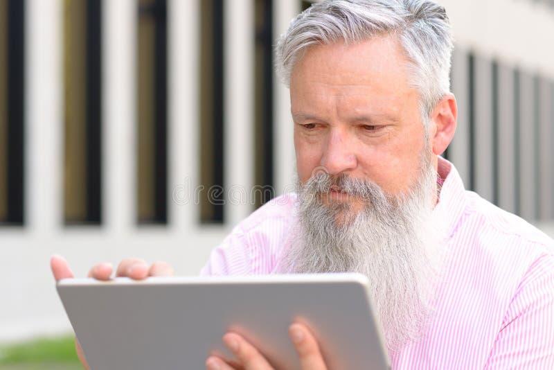 Grijs-haired gebaarde mensenlezing op een tablet stock foto's