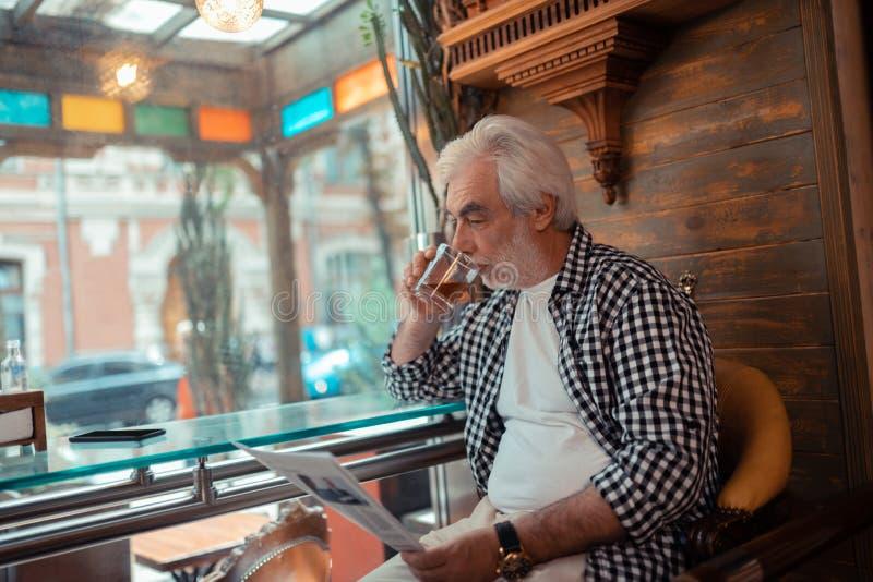 Grijs-haired mens het drinken wisky en het lezen van nieuws royalty-vrije stock foto